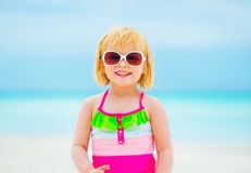 Happy baby girl in sunglasses on beach Stock Image