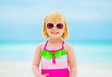 Happy baby girl in sunglasses on beach Stock Image
