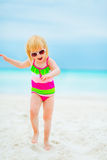 Happy baby girl in sunglasses dancing on beach Royalty Free Stock Images