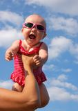 Happy Baby girl in swimsuit under clouds Stock Images