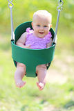 Happy Baby Girl Swinging at Playground Stock Image