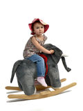Happy baby girl is swinging on see-saw.  Royalty Free Stock Photography