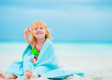 Happy baby girl in towel sitting on beach Stock Photo
