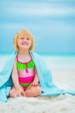 Happy baby girl in towel sitting on beach Stock Photos