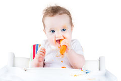Happy baby girl trying her first solid food, carrot. Happy laughing baby girl trying her first solid food, a carrot Stock Photos