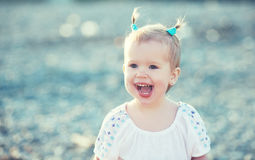 Happy baby girl with two tail hairstyle smiling at sea on the be Stock Photography
