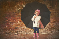 Happy baby girl with an umbrella in the rain playing on nature. Happy baby girl with an umbrella in the rain runs through the puddles playing on nature Royalty Free Stock Photos