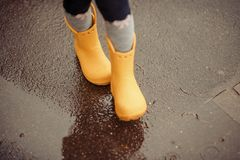 Feet of child in yellow rubber boots jumping over a puddle in th royalty free stock image
