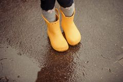 Feet of child in yellow rubber boots jumping over a puddle in th stock photos