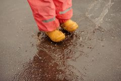 Feet of child in yellow rubber boots jumping over a puddle in th royalty free stock photo