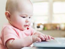 Happy baby girl using laptop computer Stock Image