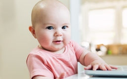 Happy baby girl using laptop computer Royalty Free Stock Photos