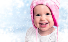 Happy baby girl in winter hat smiling on outdoors stock photography