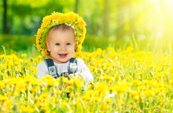 Happy baby girl in a wreath on meadow with yellow. Beautiful happy little baby girl in a wreath on a meadow with yellow flowers dandelions on the nature in the Royalty Free Stock Photography