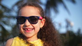 Happy baby girl in a yellow dress and sunglasses, curly hair, looks at the camera, smiling and a little shy. Child stock footage