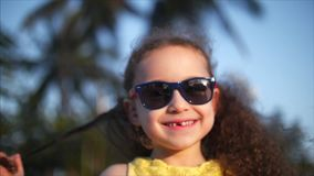 Happy baby girl in a yellow dress and sunglasses, curly hair, looks at the camera, smiling and a little shy. Child stock video