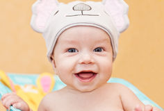 Happy baby in the hat. Sitting on an orange background royalty free stock image