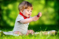 Happy baby have fun in the Park on a Sunny meadow with cherries. Royalty Free Stock Image