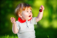 Happy baby have fun in the Park on a Sunny meadow with cherries. Stock Image