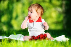 Happy baby have fun in the Park on a Sunny meadow with strawberr Stock Photo