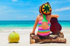 Happy baby have fun on summer tropical beach holiday. Little happy baby girl in rastaman hat has fun, play reggae music on Hawaiian guitar, enjoy caribbean beach royalty free stock photos