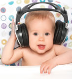 Happy baby with headphones listening to music Stock Photos