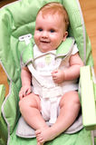 Happy baby in high chair Stock Photo