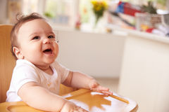 Happy Baby In High Chair At Meal Time Stock Image