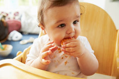 Happy Baby In High Chair At Meal Time Royalty Free Stock Image