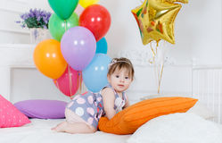 Happy baby on his first birthday. Little girl with red hair and dark eyes,wearing a gray dress with white and pink polka dots, sleeveless,sitting playing on the Stock Photography