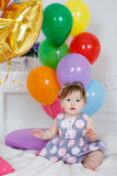 Happy baby on his first birthday. Little girl with red hair and dark eyes,wearing a gray dress with white and pink polka dots, sleeveless,sitting playing on the Royalty Free Stock Photography