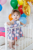 Happy baby on his first birthday. Little girl with red hair and dark eyes,wearing a gray dress with white and pink polka dots, sleeveless,standing on a white bed Royalty Free Stock Photo