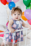 Happy baby on his first birthday. Little girl with red hair and dark eyes,wearing a gray dress with white and pink polka dots, sleeveless,standing on a white bed Royalty Free Stock Images