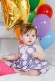 Happy baby on his first birthday. Little girl with red hair and dark eyes,wearing a gray dress with white and pink polka dots, sleeveless,sitting playing on the Royalty Free Stock Photo