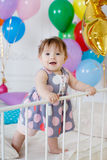 Happy baby on his first birthday. Little girl with red hair and dark eyes,wearing a gray dress with white and pink polka dots, sleeveless,standing on a white bed Stock Photo