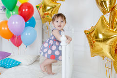 Happy baby on his first birthday. Little girl with red hair and dark eyes,wearing a gray dress with white and pink polka dots, sleeveless,standing on a white bed Stock Image