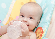 Happy baby holding bottle Royalty Free Stock Images