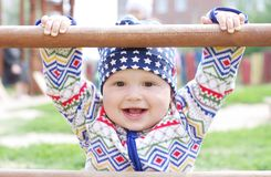 Happy baby holding of climber on playground. Happy baby age of 10 months holding of climber on playground Royalty Free Stock Images