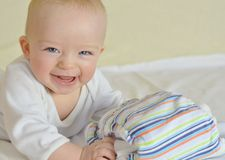 Happy baby is holding cloth diaper. Smiling six month old baby holding cloth diaper with colored stripes. White cloth and bright background Stock Images