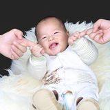 Happy baby holding parents fingers Royalty Free Stock Images