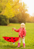 Happy baby holding red umbrella Royalty Free Stock Image