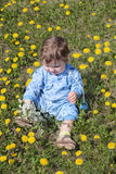 Happy baby holds flowers and sits on green meadow Royalty Free Stock Image