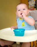 Happy baby infant boy eating meal. While sitting in high chair Royalty Free Stock Photography
