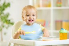 Happy baby kid boy eating food itself with spoon. Happy cute baby kid boy eating dood itself with spoon royalty free stock images