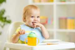 Happy baby kid boy eating itself with spoon. Happy cute baby kid boy eating itself with spoon royalty free stock photography
