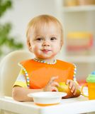 Happy baby kid boy toddler eating itself with. Happy cute baby kid toddler eating itself with spoon stock images