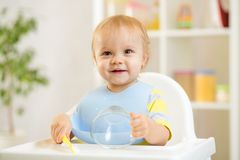 Happy baby kid boy waiting for food with spoon. At table royalty free stock image