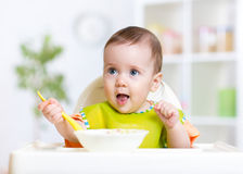 Happy baby kid eating food itself with spoon Royalty Free Stock Photo