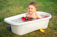 Happy baby laughing and holding toy car in the bath Royalty Free Stock Photography