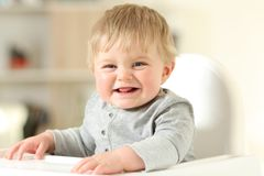 Baby laughing looking at camera on a chair. Happy baby laughing looking at camera on a high chair at home Royalty Free Stock Photos
